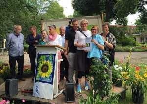 Bezirksstadträtin Sabine Smentek (r.) übergibt den Umweltpreis Mitte an Cecilia Stickler (3. v. r.) und die Kümmerer vom Vinetaplatz.