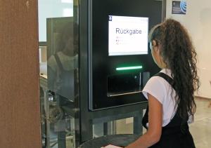 Ein Mädchen probiert den Rückgabeautomaten aus.