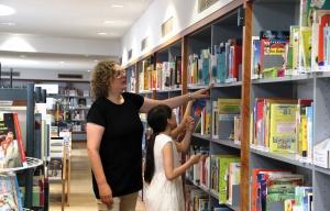 Birgit Thomsmeier hilft einem Mädchen, ein Buch im großen Bücherregal zu finden.