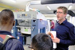 Wolfgang Schulz zeigt einer Gruppe die Druckerei.