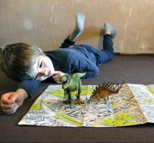 Jakob lässt seine Spielzeugdinos über die Karte des Brunnenviertels laufen und überlegt, wo die echten DInosaurier früher überall gelebt haben könnten. Foto: Dominique Hensel