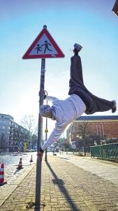 Parkour-Sportler Alex an einem Verkehrsschild vor dem Stadtteilladen des Quartiersmanagements Brunnenstraße. Foto: Paul Alpha